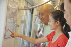 Granddaughter with grandparents standing in the subway and looking at the map Stock Image