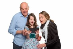 Granddaughter and grandparents using tablet royalty free stock photo