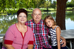 Granddaughter With Grandparents. A young girl sits at a picnic table in the park with her grandparents. They are wearing red, white, and blue. The picnic table Stock Image