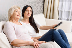 Granddaughter and granny watching TV together Stock Photo