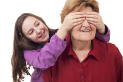 Granddaughter hands over grandmother eyes close up. Isolated stock photo