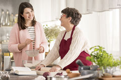 Granddaughter helping grandma in a kitchen. Happy granddaughter helping grandma in a modern kitchen stock photo