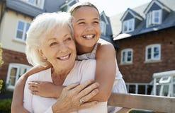 Granddaughter Hugging Grandmother On Bench During Visit To Retirement Home