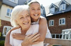 Free Granddaughter Hugging Grandmother On Bench During Visit To Retirement Home Royalty Free Stock Photos - 134202688