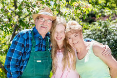 Granddaughter hugging grandparents in a summer garden. Royalty Free Stock Photography