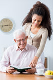 Granddaughter keeping his grandpa company. Image of granddaughter keeping his grandpa company stock photography