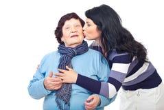 Granddaughter kissing grandmother stock image