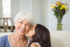 Granddaughter kissing grandmother on cheek in living room Stock Photos