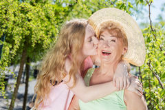 Granddaughter kissing grandmother in a summer garden. Royalty Free Stock Photography