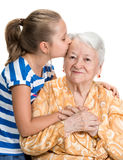 Granddaughter kissing her old grandmother Stock Image