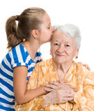 Granddaughter kissing her old grandmother Royalty Free Stock Photo
