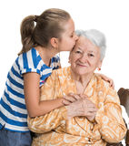 Granddaughter kissing her old grandmother Royalty Free Stock Photos