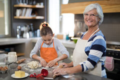 Granddaughter kneading dough. Smiling granddaughter kneading dough while standing with grandmother Royalty Free Stock Photography
