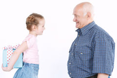Granddaughter making a present to grandfather Stock Images
