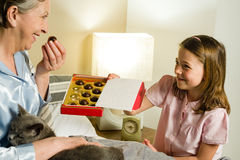 Granddaughter offering pralines to grandmother Royalty Free Stock Photography