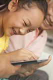 Granddaughter playing on digital tablet with grandfather Royalty Free Stock Photo