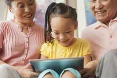 granddaughter playing on digital tablet with grandparents Stock Images