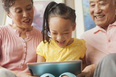 Granddaughter playing on digital tablet with grandparents Royalty Free Stock Image