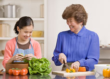 Granddaughter preparing salad with grandmother. Helpful granddaughter preparing wholesome salad with grandmother in kitchen for dinner Stock Photo