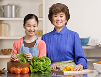 Granddaughter preparing salad with grandmother. Helpful granddaughter preparing wholesome salad with grandmother in kitchen for dinner Stock Images