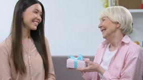 Granddaughter presenting gift box to grandmother, anniversary celebration. Stock footage stock video