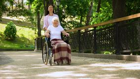 Granddaughter pushing old woman in wheelchair hospital garden, support and care. Stock footage stock video