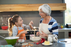 Free Granddaughter Putting Flour On Grandmothers Nose Stock Photography - 97400572