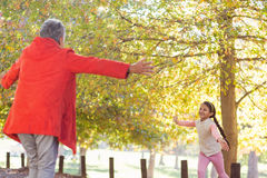 Granddaughter running towards grandmother at park Royalty Free Stock Photo