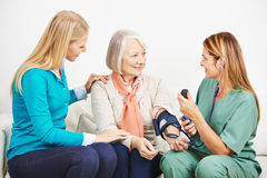 Granddaughter and senior woman with nurse Royalty Free Stock Images