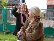 Granddaughter showing kohlrabi to granddaughter Royalty Free Stock Photography