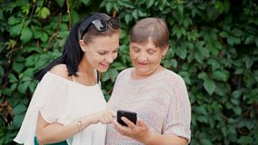 Granddaughter shows old grandmother something in smartphone, teaches her to handle with modern gadget and technology royalty free stock images