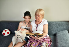Granddaughter sit next to her grandmother on the couch and read Stock Photos