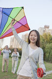 Granddaughter smiling and looking at camera and holding a kite with grandparents in the background Royalty Free Stock Images