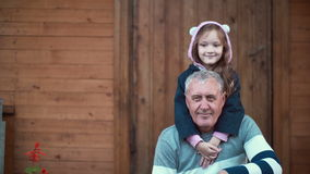 Granddaughter standing behind grandfather and hugs old man and smile. Girl bands and male kiss her hand. 4K. Cute granddaughter standing in porch of house behind royalty free stock photo