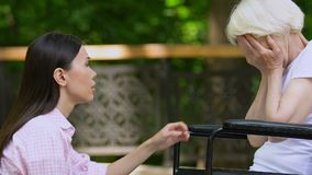 Granddaughter supporting crying old woman in wheelchair, psychological problems. Stock footage stock video footage