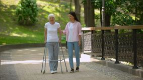 Granddaughter supporting disabled grandma with walking frame, day in park. Stock footage stock video footage