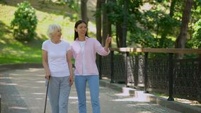 Granddaughter talking to aged woman walking with stick in park, old age health. Stock footage stock video