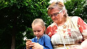 Granddaughter teaches grandmother to manage smartphone on touch screen stock video