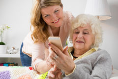 Granddaughter teaching grandma how to use smart phone stock photos