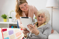 Granddaughter teaching grandma how to use tablet computer stock images