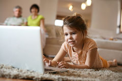 Granddaughter using laptop in living room. Stock Photos