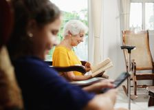 Granddaughter Using Mobile Phone And Grandma Reading Book. Family relationship between grandmother and granddaughter. Grandma reading book and female grandchild Stock Photo