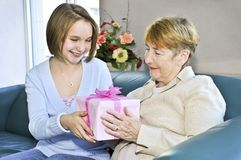 Granddaughter visiting grandmother. Granddaughter giving a present to her grandmother Stock Photos