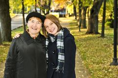 Granddaughter walking with grandmother. Teen granddaughter walking with grandmother in autumn park Royalty Free Stock Photography