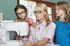 Granddaughters looking at grandmother sewing cloth Stock Image