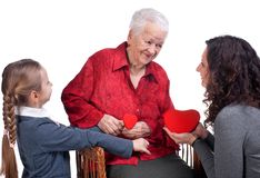 Granddaughters presenting hearts to their grandmother Stock Images