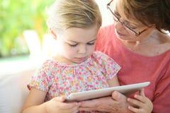 Granddaugter und ihre Großmutter, die auf einer Tablette spielen Stockfotografie
