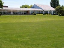 Grande área da grama pelo edifício Imagens de Stock