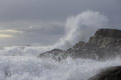 Grande éclaboussure de vague contre la falaise photographie stock