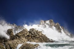 Grande éclaboussure se brisante orageuse dramatique de vagues Kleinmond, le Cap-Occidental, Afrique du Sud photographie stock